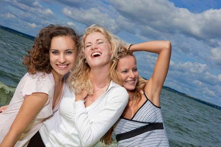 tres agradables caucásicas deportivas señoritas divertirse fuera y descanso cerca de orilla de playa juntos y sonrientes felizmente