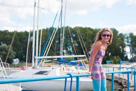 young and sensual blond caucasian girl standing on the pier near yacht dock and smiling photo