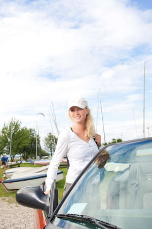cabrio: young pretty and beautiful caucasian blond girl with positive facial expression in front of the cabrio car.