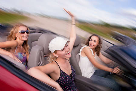 cabriolet: three happy and sensual caucasian girlfriends having drive on a red cabriolet car with bright positive expressions. shoot made on location with strobes Stock Photo