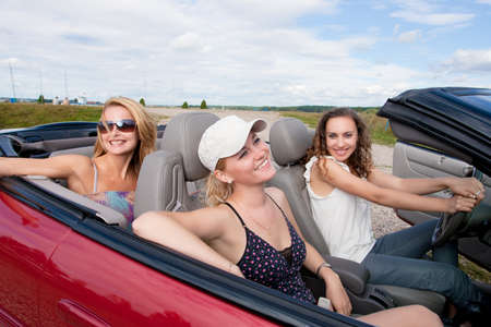 three happy and sensual caucasian girlfriends having preparing for a drive on a red cabriolet car with bright positive expressions. shoot made on location with strobes photo