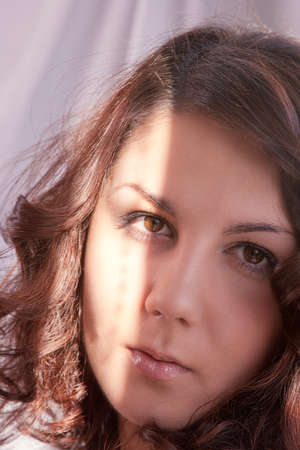 sensually: sensually looking eyes closeup of young caucasian brunette woman standing in front of window lit with a sunshine