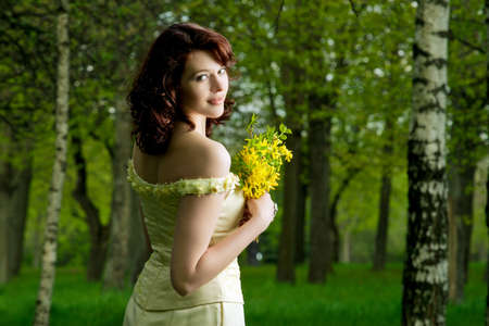 portrait of a sensual  brunette caucasian girl in wedding dress standing with flowers in spring forest-outside photo