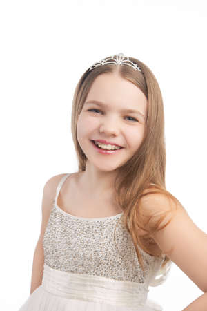 young cute female blond kid in white dress wearing artistic crown with dental teeth braces, isolated