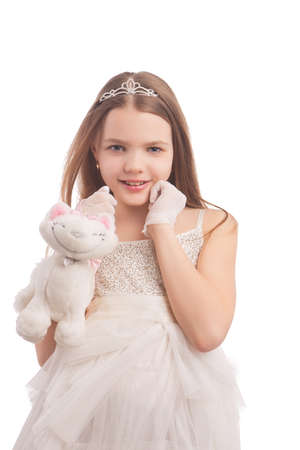 age 10 12 years: young cute female blond kid in white dress wearing artistic crown with dental teeth braces, isolated
