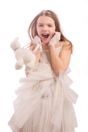 young cute female blond kid in white dress wearing artistic crown with dental teeth braces, isolated Stock Photo - 9885485