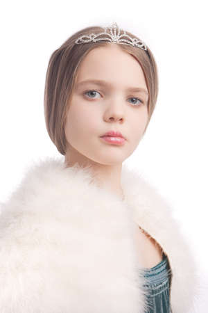 10 to 12 years: closeup of young blond little girl seriously looking and wearing crown and white fur scarf,isolated