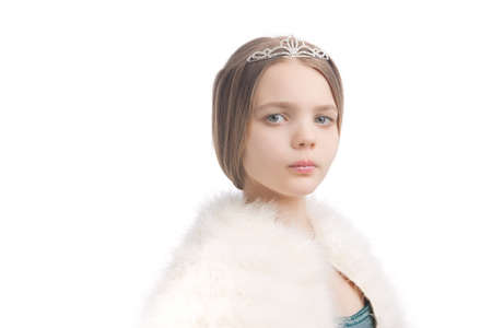 age 10 12 years: closeup of young blond little girl seriously looking and wearing crown and white fur scarf,isolated