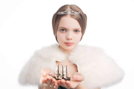 age 10 12 years: closeup of young blond little girl holding sail vessel in hands showing protection, isolated over white background