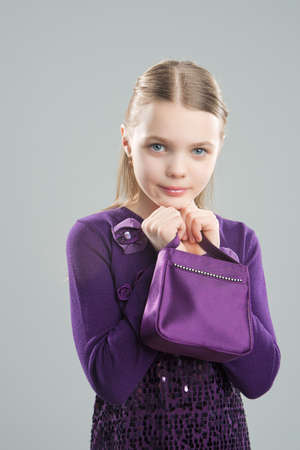 portrait of little cute girl standing holding handbag isolated over gray background