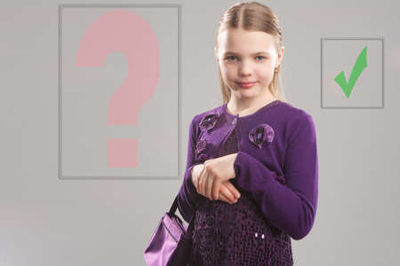 portrait of little cute girl standing holding handbag isolated over gray background photo