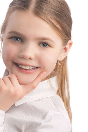 young cute caucasian blond girl wearing teeth braces standing in white shirt isolated over white background smiling Stock Photo