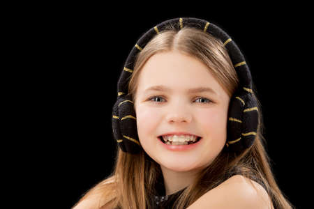 portrait of young happy caucasian blond little girl wearing teeth brackets and sitting in front of black background Stock Photo