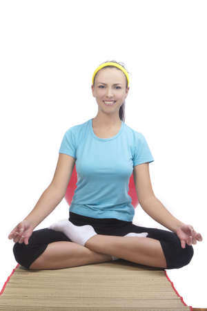 portrait of  brunette woman sitting on mat and doing yoga exercise isolated over white background