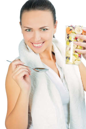 hand lifted: closeup portrait of young brunette woman holding glass filled with fruit colorful salad isolated over white