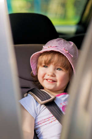 young little girl i car safety seat smiling Standard-Bild