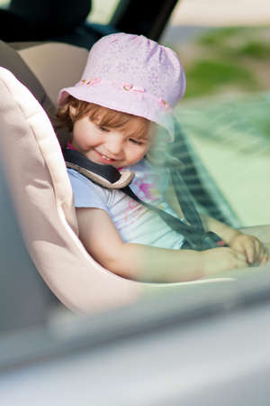 laughing little kind sitting in safety seat photo