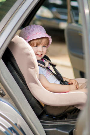 strapped: little cute girl in cap sitting in the car in child safety seat and smiling
