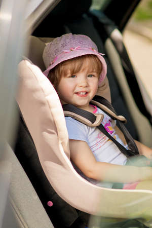 little girl in safety auto seat with smile siting Standard-Bild