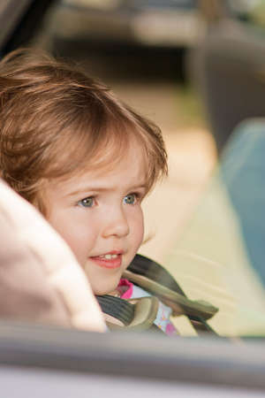 little girl portrait sitting in safety seat  and looking over window pane Stock Photo