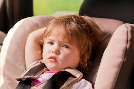 close-up portrait of young little girl kid with tired expression sitting in safety seat Stock Photo