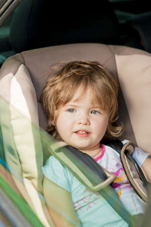 little girl sitting in car safety seat.shot made through window pane photo