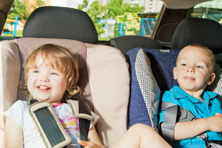 two little kids sitting on back seat in child safety seats looking on windows photo