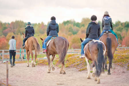 four young girls learning to ride on horse outside accompanied with guide