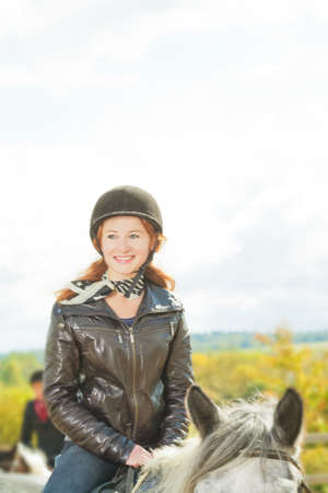 young red haired jockette smiling  and riding a horse outdoors with pleasure on a sunny autumn weather photo
