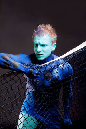 faceart: young handsome man with mozaic bodyart and face-art painting standing in front of black background holding net: bodyart project