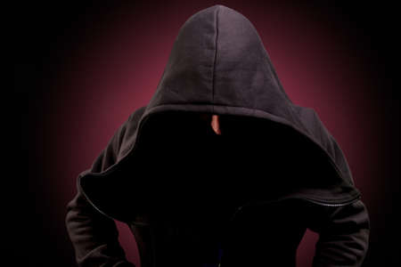 man in black biggin with hidden face over dark background