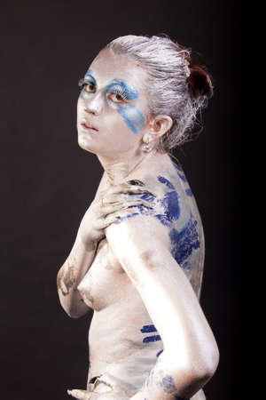 nu: caucasian young woman with acrylic paint on body, hair and  face Stock Photo