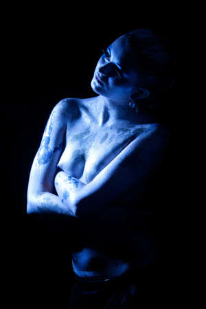 sensual and sexy  young caucasian woman painted with acrylic paint and standing over black background.shot made with cold light temperature photo