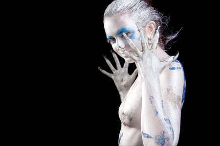 expressive positive caucasian young woman with body art painting isolated over black photo