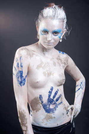 shaped caucasian young woman with acrylic paint on body, hair and face photo