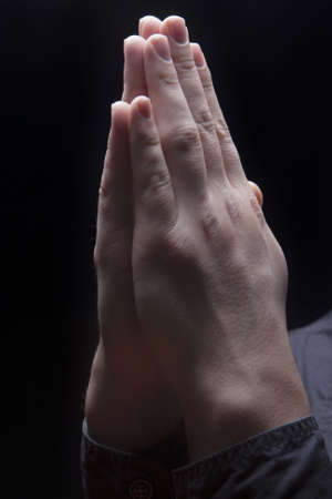 hands of a young man folded together in prayer isolated over black background photo