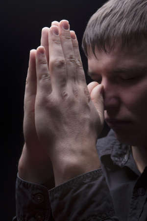 young man praying with hands connected in front of the face and standing isolated over black photo