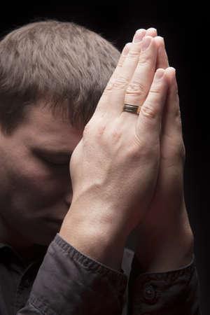 hombre orando: hombre joven orando con las manos conectadas por delante de la cara y de pie aislado m�s de negro Foto de archivo