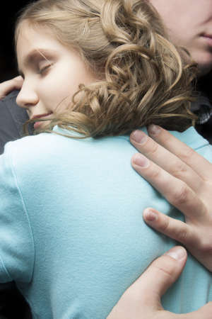father and daugther together embracing over black background