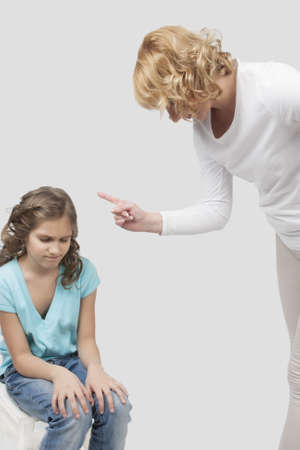 mother instructs her teenage daughter by threatening with a finger standing against light gray background Stock Photo - 13522787