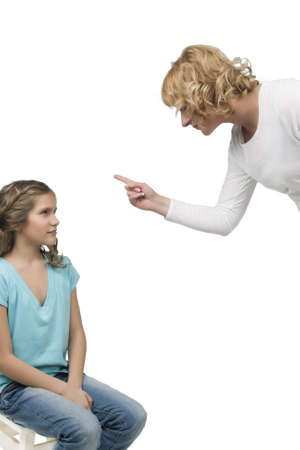 mother instructs her teenage daughter by threatening with a finger standing against light gray background Standard-Bild