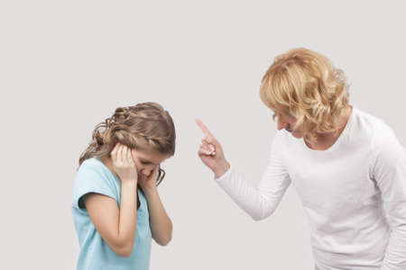 mother preaches her teenage daughter by threatening with a finger pointed directly on girl with closed ears standing against light gray background Stock Photo - 13522761