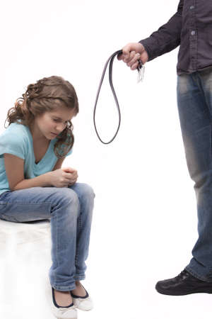 father holding belt to threaten her teenage daughter sitting downwards and fearing isolated on white photo