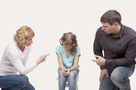mother and father preach their young teenage daughter with a morality sitting on hunkers and isolated over white background Stock Photo - 13522795
