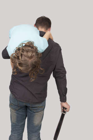 father holding her teenage daughter flpped over a shouder trying to punish her using a belt isolated over light background Stock Photo - 13522789