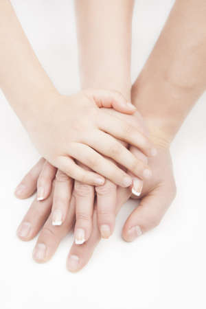 three hands connected together put in stack one over another over white