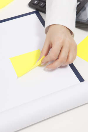 hand of young female woman using yellow sticker to attach it to a white paper sheet on table Stock Photo - 14302743