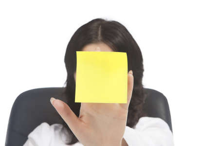 hand lifted: portrait of young brunette caucasian girl holding sticker note in front of her face, isolated on white background