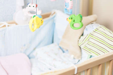 lullaby: child cradle with toys hanging around Stock Photo