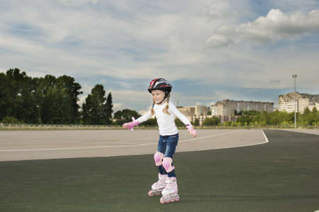 portrait of small little caucasian blond girl skating outside on stadium track in protective helmet photo